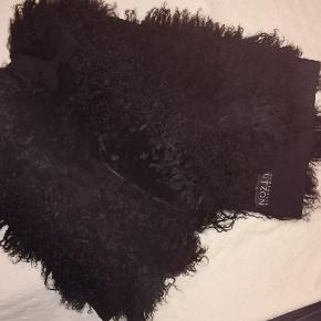 Langt sort tørklæde. Tibetlam på den ene side, vandsæt stof på den anden. Aldrig brugt.