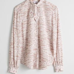 Jeg sælger denne fine skjorte fra & Other Stories i str. 34.  Den er hvid/beige med zebra print og med bindekrave.   Skjorten kan sendes eller afhentes på Islands Brygge.