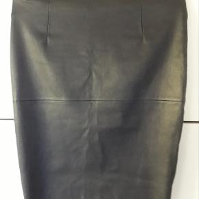 """Smukt Pencilskirt i stretch-læder (100% lammeskind) fra Malene Birger.  Modellen hedder """"Dolila"""" og er med lynlås midt bag. Meget elastisk. Så nederdelen bliver tætsiddende.  Den kan dresses både op og ned. Så den en meget anvendelig. Nederdelen er anført som brugt men god!. Jeg overvejede faktisk, at skrive som ny. Nederdelen er ikke imprægneret.  Mål: Talje på """"spændbøjle"""" 90 cm. Talje læggende flat ned 86 cm. Hofte V/syning 100 cm Bund 88 cm. Længde 64 cm.  Alle målene kan strækkes mere"""