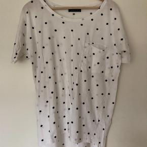 Varetype: Bluse Farve: Hvid  Fin t shirt med sorte prikker i god stand. Lidt længere bagpå.  Passes af både XS - M  Bytter ikke Handler via mobilepay og sender med dao