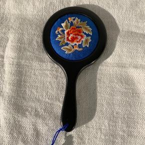 Lille sortmalet håndspejl. Bagsiden er blåtstof med blomsterbroderi. Der er en fin lille opbevaringspose med. Længde 15 cm diameter 8 cm. Pris kr 75