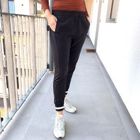 Comfy sorte bukser fra SUIT med ribkant og lynlås.