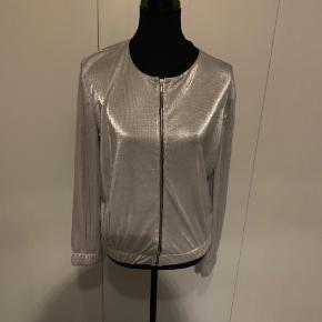 Ny jakke med lynlås i sølvlook fra Atmosthere str 38.  Sort kant ved krave og elastiskkant ved ærmer og for neden.  Køber betaler Porto.