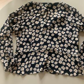 Fin bluse med syning i taljen, der giver figur.