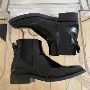 """Smukkeste støvler fra Ganni 🖤  Helt overordnet set er støvlen i rigtig god stand og passet godt på. MEN desværre er den lille flap bag på """"revet"""" op på den ene sko - se billeder. Jeg har bundærligt først opdaget det nu, da jeg har taget billeder, så det er ikke rigtig noget man ser, når skoen er på.   Str 40, men jeg bruger normalt 39 💛  Kunne godt bruge en omgang skosværte - det har jeg bare desværre ikke selv.   Afhentes på Nørrebro eller sendes via TS-handel, hvor sælger betaler fragt+gebyr. Bytter ikke."""