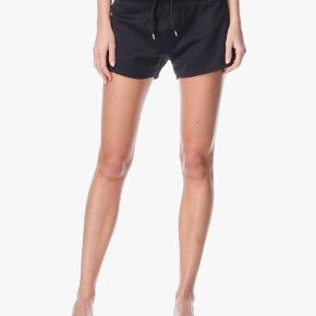 Fine sporty shorts fra Filippa K, str s. Lynlås bag på den ene side. Model: shiny sweat