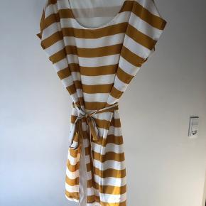 Smuk stribet kjole fra soaked in luxery med bindebånd til taljen. Farven er hvid og karrygul og kan bedst ses på billedet der er taget tæt på.