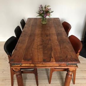 Rustikt træbord i eksotisk træ. Sammensat med jernsøm. Ben kan skrues af. Lignende bord, modellen større, set vurderet på Lauritz.com til 10.000.   Mål: 182x90