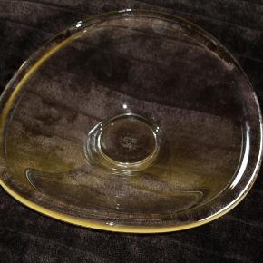Varetype: Per Lütken fad.. Størrelse: 35 x 37 cm Farve: Klar  Meget flot Selandia fad i klar glas fra Holmegaard - Per Lütken med hans autograf i bunden.  Det måler godt 35 x 37 cm.  Er brugt og lidt ridset, ellers fejler det intet.  Prisidé 500,-kr. Foretrækker at det afhentes :-)
