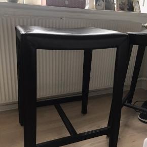 Den er beklædt med sort læder på sæde og ben. På sæde kan det ses at sædet har været siddet på. Der er 2 barstole, som sælges samlet. De er 59cm høje, sædet er 45 x 33 cm