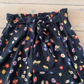 Super søde blomstrede bukser med bindebånd og elastik i taljen.  Går lige til anklerne, så de er perfekte til en lidt kølig sommerdag.  Har selv været rigtig glad for dem.