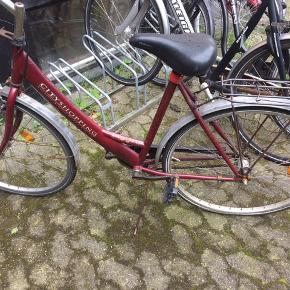 Cykel i rød, lidt rust (se billeder), gearet virker, og gode bremser. Desværre er hjulene flade, hvorfor den er så billig. Det kan lappes og laves ved cykelsmed.