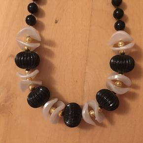 Super fin lang vintage halskæde med dekorative perler i plast i farverne perlemor, sort og guld. Formentlig fra 1980'erne. Kom med et bud.   Varen befinder sig i 9520 Skørping. Sender med DAO.  Se også min øvrige annoncer. Jeg sælger tøj, sko og accessories. Pt er min shop fuld af retro og vintagekup, high street fund og mærkevarer i mange forskellige str. Kig forbi og spøg endelig!!