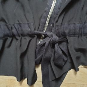 Bikerjakke fra Sonia Rykiel af silke. Den måler 100 om brystet og er 56 cm lang. Har bindebånd i taljen og lynlås nederst på ærmerne. Tænker den måske er en lidt lille 42, så kig på målene.  Ny Pris m: 3000,- Sælges for 975,-