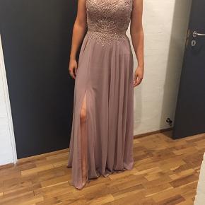 """Smuk lyserød gallakjole/festkjoler, købt i """"La Princessa"""" i Aarhus. Den er brugt en gang og vasket efterfølgende. Kjolen er en størrelse 8, og passes af en str. 38. Ny pris: 2200."""