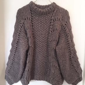 Hjemmestrikket sweater i Ganni lignende mønster og snit. Farven er en blanding af grå og lilla. Farven vises bedst på det sidste billede. Den er i toplækkert uld. Drops Eskimo garn.   Størrelsen er en xsmall/small.