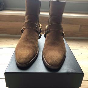 Saint Laurent Wyatt Harness boots i ruskind fra 'Surf Sound' kollektion fra SS16.  Støvlerne er i en str 41, men vil også kunne passes af en 42.  Der er sat såler på støvlerne, på både fronten og hælen af støvlerne for, at beskytte sålen.  De er brugte, men de er i en fin stand imo - brug endelig billederne til at lave egen bedømmelse.  Box og dustbag medfølger.