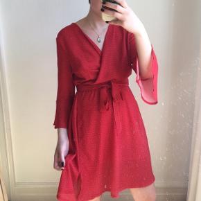 Rød slå-om-kjole med små hvide stjerner. Den er købt i Amsterdam og har aldrig været brugt. Den minder om kjolerne fra Realisation Par. Størrelse L. Sælges, da den desværre er for stor.