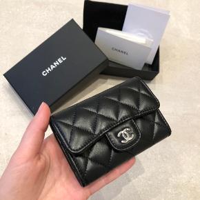 Smuk klassisk Chanel kortholder / pung i sort lammeskind med sølv hardware og burgundy-farvet 'interiør'.  Pungen er som ny 🖤  Æske, dustbag og kvittering medfølger.  Kan afhentes i Aalborg eller sendes via Trendsales handelssystem.