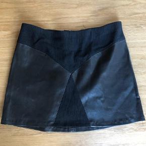 Varetype: Kort nederdel Farve: Sort Oprindelig købspris: 1200 kr.  Lækker kort ægte læder nederdel  Str 38.  Fra Utzon den er 35 cm lang  Lynlås bag på