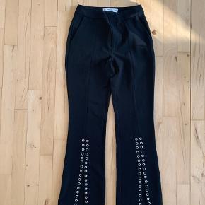 Bukser med bræde ben. Tætsiddende på lår. Brugt én gang