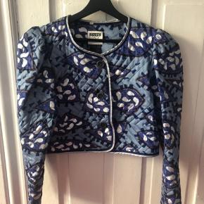 Fantastisk lille quiltet vintage jakke. Mønster i blåt, brunt og sølv på dueblå. Tætsiddende med masser af puf øverst i ærmet. Vil passes af en 36 eller 38. God stand. Pris 400.