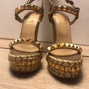 Chistian Louboutin Cataclou 140 sandal med kilehæl. Hælen måler cirka 140 mm med en 40 mm plateau under forfoden.   Sandalerne sælges med alt originalt tilbehør - kasse, stofposer og ekstra hæle  Cataclou sandalerne er beklædt med nitter i guld, guldfarvet skind og flet. Sandalerne er super feminine og elegante. De er nemme at gå, trods den høje hæl, fordi de er med kilehæl.