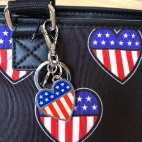 Flot tote fra Love Moschino, fra serien cuori: American Heart kollektion 2014/2015. ALDRIG BRUGT, mærken sidder stadigvæk på. se billeder. lavet af canvas og imiterede læder. høj kvalitet. dustbag følger med. se mål:  højde: 22 cm. længde: op på tasken: 40 cm længde i bunden: 25 cm. dybde: 18 cm i bunden. ny pris på tasken var ca. 1450 kr. byttes ikke