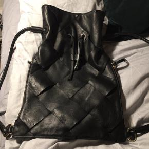 - Sort ægte læder taske / backpack med lommer siderne, lukkes med strap  - Brugt få gange  - Kan bruges som rygsæk og skuldertaske