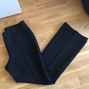 Habitbukser med flare i benene   Str. 42, passer nærmere 38-40  Aldrig brugt   Farve: mørkeblå med camelfarvet/brune striber