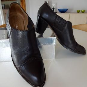 Næsten som nye Budapester sko/lave støvletter fra 'ANTONI DE LUCA' - str. 40 - i flot mørkebrunt læder 6 cm hæl - elastik i siderne Kun brugt ganske lidt - minimale brugsspor på hælene ellers som nye :-)
