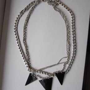 Fed og rå statementhalskæde af sølvfarvet metal bestående af 3 lag, der hænger sammen. 3 trekantede sorte vedhæng. Mål: 48 cm i diameter. Kun brugt et par gange.