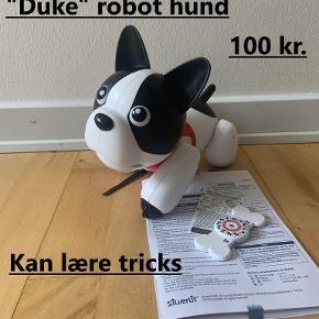 Super sej interaktiv hund med navnet Duke. Hunden kan lære tricks og at kende barnets stemme. Giv Duke kommandoer via kødbenet. Når du rører ved sensoren på Dukes hoved, viser han forskellige former for følelser. Med 10 livlige former for bevægelser. Kan synge og danse.  Brugt få gange og har ellers bare stået i et skab.  Nypris: 400 kr. Sælges for 100 kr. ved afhentning i Herning.