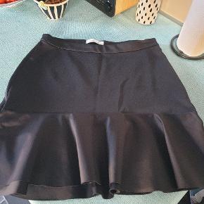 Mega sød nederdel i et glat blankt sort stof. Brugt én gang. SÅH fin.