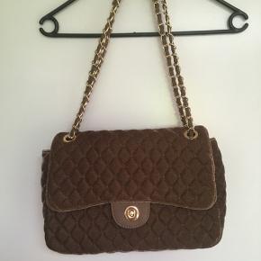Smuk brun  taske i velour sælges. Bredde 34 cm. Højde 22 cm Dybde 9 cm. Kun brugt få gange, så flot som ny:-) Sender også  gerne ved betaling med MobilePay+ Porto GLS  39 kr. Er købt i Frankrig, men jeg kan ikke huske, hvilket mærke.