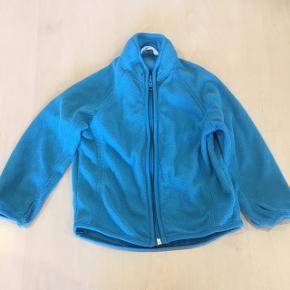 Fin lille fleecetrøje med hul til tommelfingre, så den bliver hvor den skal hvis jakken skal ovenover.  Str. 86/92