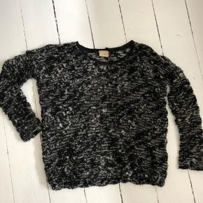 Fed strik i sort med nistre / mønstre i sølv, hvid og grå. Elastik i talje, så den poser