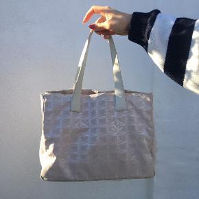 Chanel canvas Tote i svag lyserød med hvide håndtag har minimal slid i kanten, ikke noget man lægger mærke til. Der kan lægge en MacBook Air med cover i så den er perfekt som skole taske. Mål: 25 x 15 x 35 cm. Selfølgelig 100 % ægte. Der følger ikke noget med tasken.