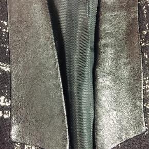 Lun blazer i 90'er stil i sort/hvid med fede detaljer - god til efterår og vinter. Fra en gammel Zara kollektion - ca. 15 år gammel. Kan lukkes foran med en hægte. Brugt få gange og fremstår uden brugsspor.