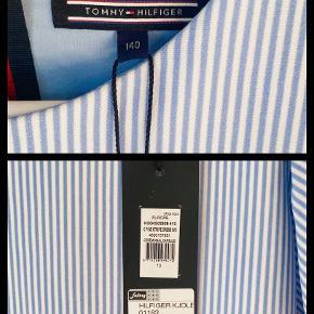 Helt ny kjole fra Tommy Hilfiger.  Lækker kvalitet med stretch, flotte snit og perfekt pasform.  Desværre købt for stor og fik ikke byttet inden tidsfristen, så sælges derfor billigt.   ***Pris kun 350,-*** (Købspris 800,-)   Str 140 / 10 år  Materiale:  100% bomuld 6% Elastan   Kontakt 50413100 Afhentning Østbirk  Forsendelse DAO 39,-