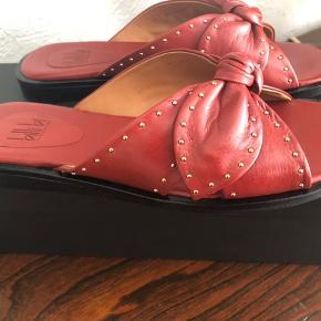 Skind sandal i terracotta/rustrød farve med guldnitter. Str. 38, aldrig brugt stadig i æske. Bytter ikke. Ny pris 1100 kr. mp. 500 kr.