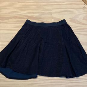 Kort nederdel i joggingagtigt stof. Stort set som ny.