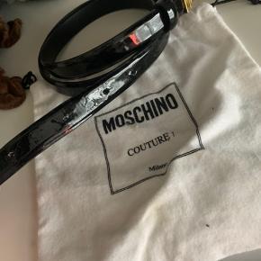 Moschino bælte, rigtig fin stand. Har dog prøvet at lave et par huller i selv, som man kan se på det ene billede - men dette er ikke noget man lægger mærke til overhovedet.  Bæltet er str 105 og original dustbag medfølger.