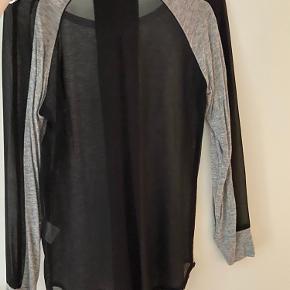 Virkelig din bluse str 34.  Blusen er grå med gennemsigtige mesh detaljer ved ærmer og ryg.  Den er brug få gange.