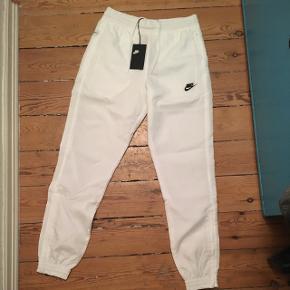 Flotte hvide Swoosh Woven Trackpants fra Nike. De er store i str., jeg bruger selv S-M. Aldrig brugt med prismærke. Købspris er 600, kom med bud! Sender eller kan afhentes på Nørrebro 😊