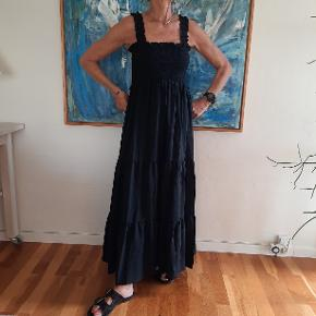 Feminin maxi kjole i viscose og nylon med isyet skørt, smock syning ved brystet, stropper og flæsedetaljer. Til salg i flere grupper.
