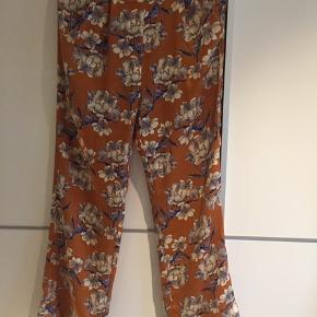 Flotte bukser med elastik bagerst i taljen og brede ben. Læg øverst og sidelommer.  Sælger også tilhørende skjortejakke / blazer.  Sælges samlet for 300 + porto