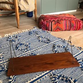 Super fed retro hylde i teaktræ og med holdere i messing 🌸 Rigtig fed retro sag! Har en reparation foran i det ene hjørne (se billede 5) og træet har nogle ridser og pletter. Kan med fordel gives en omgang olie mere, jeg har lige givet den på første og sidste billede ☺️ den ene holder er lidt skæv, men den fungerer uagtet. Måler ca. 20 x 60 cm.   Bemærk - afhentes ved Harald Jensens plads. Bytter ikke 🌸   💫 Retro loppe lopper loppefund teak teaktræ teaktræsmøbel teaktræshylde hylde hylder messing