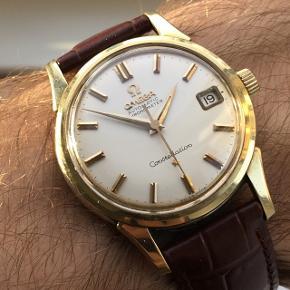 Et utroligt flot, klassisk og eftertragtet Omega Constellation i guld på stål sælges! Uret er i en helt utrolig flot stand med en helt perfekt skive (uden patinering) med datovisning samt gyldne visere og indeks. Constellation serien var Omegas absolutte topmodel indenfor dress-ure.  Kassen er en 14 kt. guld på stål kasse, hvilket vil sige at bezel (den øverste del af uret) er 14 kt. massivt guld. Det er derfor en helt, helt anden kvalitet end ure med gulddoublé, da guldet på dem blot er tyndt lag som kan slides væk. På bagsiden har uret den kendte Genève Observatorium i massivt 18 kt. guld. Både kronen og glasset er originalt Omega. Værket er et chronometer certificeret cal. 551, som holder tiden helt som det skal.  Årgang: ca. 1960 Størrelse: ca. 34,5 mm uden krone Ref. nr.: 14393 - SC Cal. nr.: 551  Uret kommer på en sprit ny brun Hirsch rem i en rigtig god kvalitet.  Uret kan beses og afhentes i Aarhus C, men ellers sender jeg også GRATIS uret til hele landet med forsikring og track and trace. Hvis der skulle være spørgsmål, er det naturligvis blot at kontakte mig.  Ingen skambud, tak! 🙂