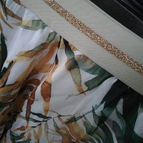 Flot nederdel med elastik i taljen, smukt print og glimmer detalje.